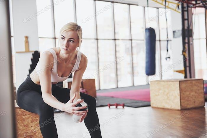 Foto von attraktiven Fitness-Frau im Fitness-Studio hält Flasche Wasser