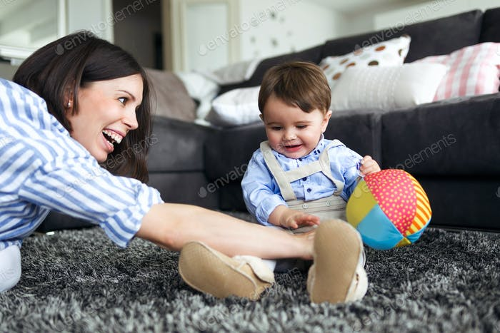 Happy young mother with her baby playing on the floor of living room at home.