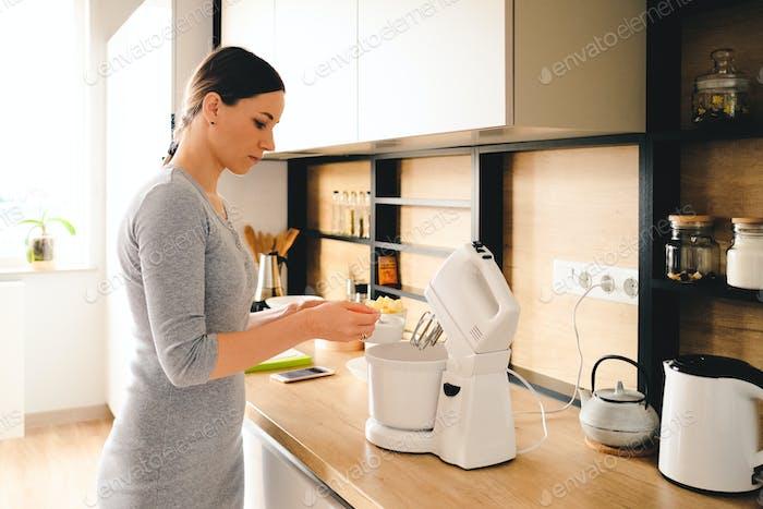 Authentische Frau mit einem Handmixer