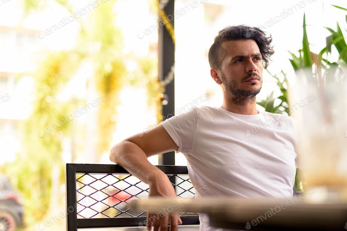Handsome Turkish man with curly hair relaxing at the coffee shop