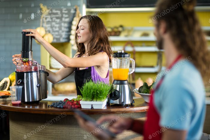 Shop assistant preparing juice at health grocery shop