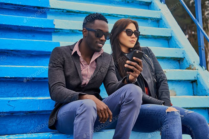 Caucasian female and Black male sits on a step and using smart p