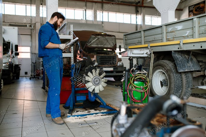 Young serious worker of automobile repair service reading instructions