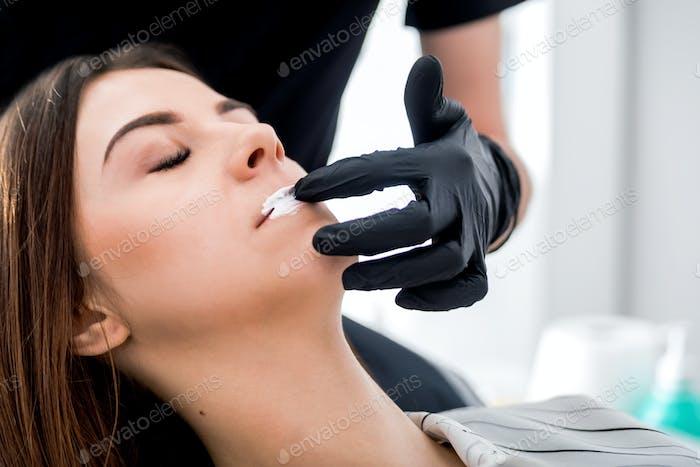 Applying anesthesia before enlarging lips at beauty salon