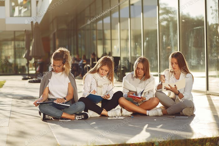 Four students on a student campus with a tablet
