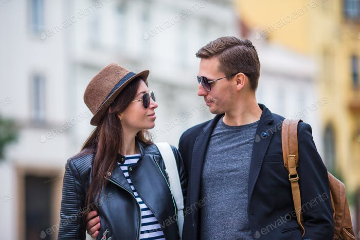 Happy couple walking in Europe. Smiling lovers enjoying cityscape with famous landmarks