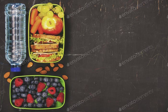 Sandwich, apple, grape, carrot, berry in plastic lunch box and b
