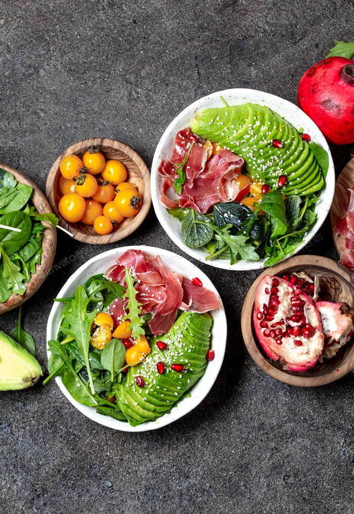 Low carbs bowl. Fresh salad with green spinach, rucola, avocado an ham serrano in white bowl, gray