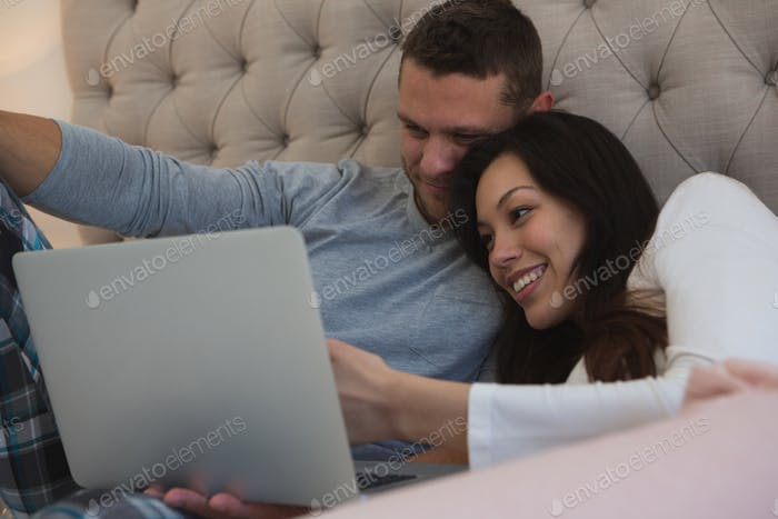 Couple using laptop in bedroom at home