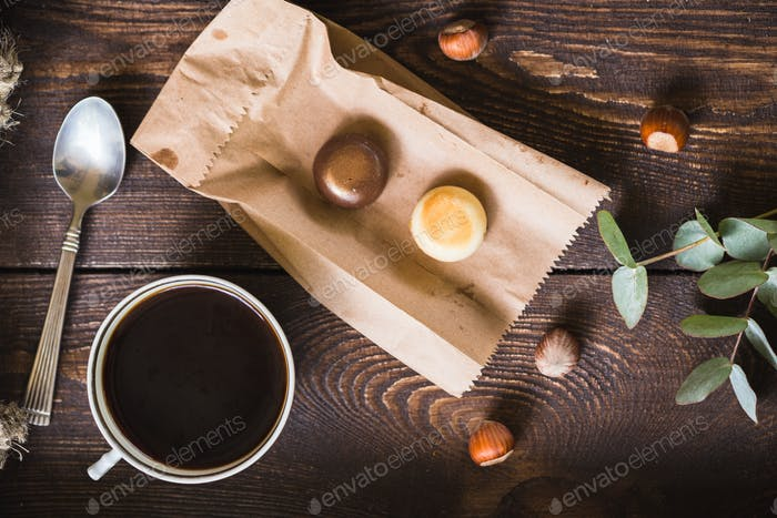 A cup of coffee and candies on a brown tray.