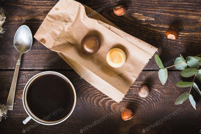 Eine Tasse Kaffee und Süßigkeiten auf einem braunen Tablett.