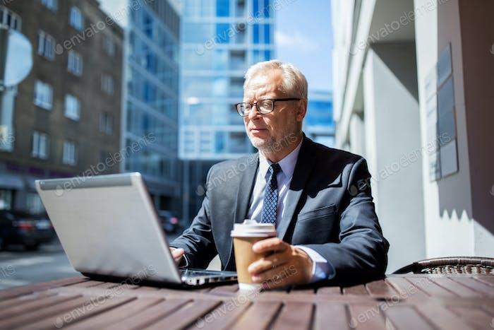 Senior Geschäftsmann mit Laptop trinken Kaffee