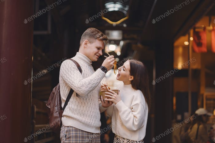 newlywed couple eating noodles with chopsticks in Shanghai outside a food market