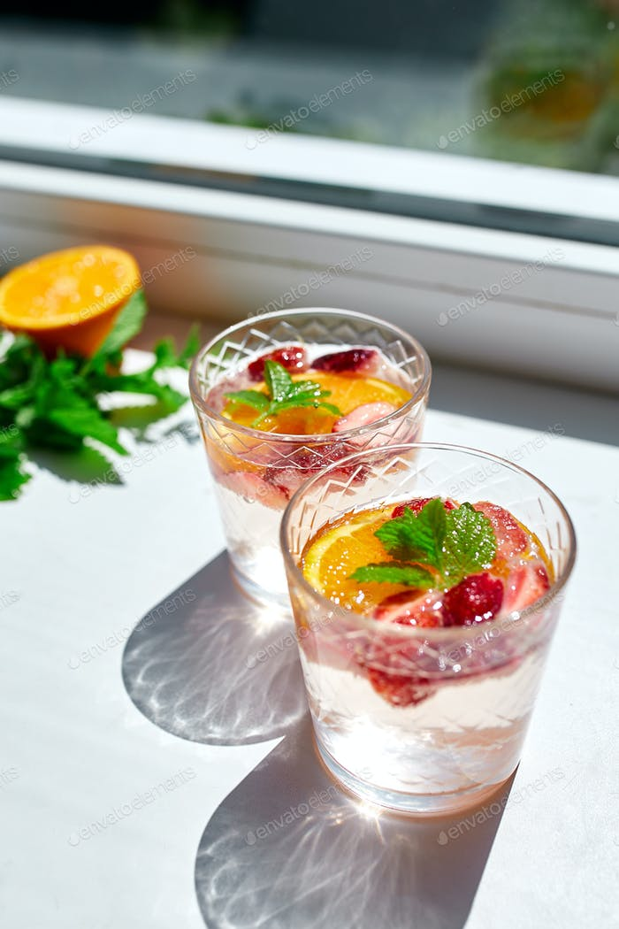 Summer cocktail with strawberry, orange and mint in glass