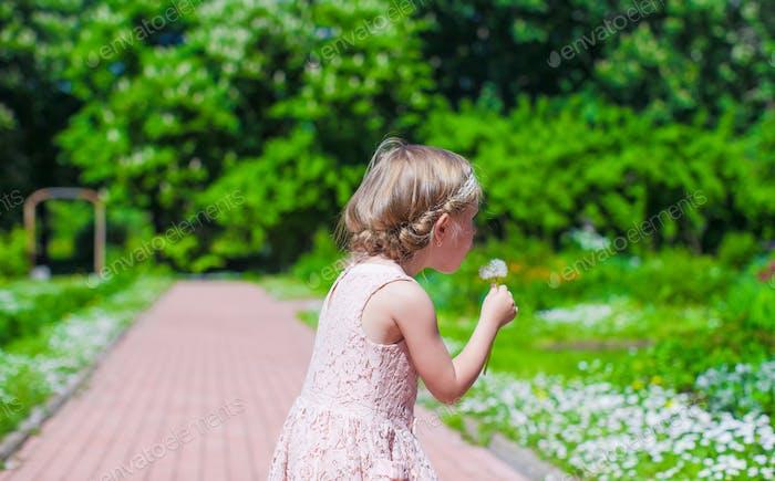 Little girl blowing a dandelion outdoor