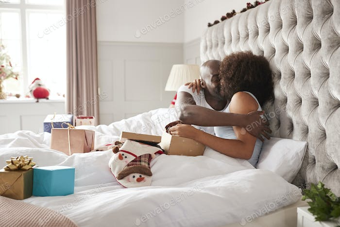 Young black couple sitting up in bed embracing on Christmas morning, selective focus