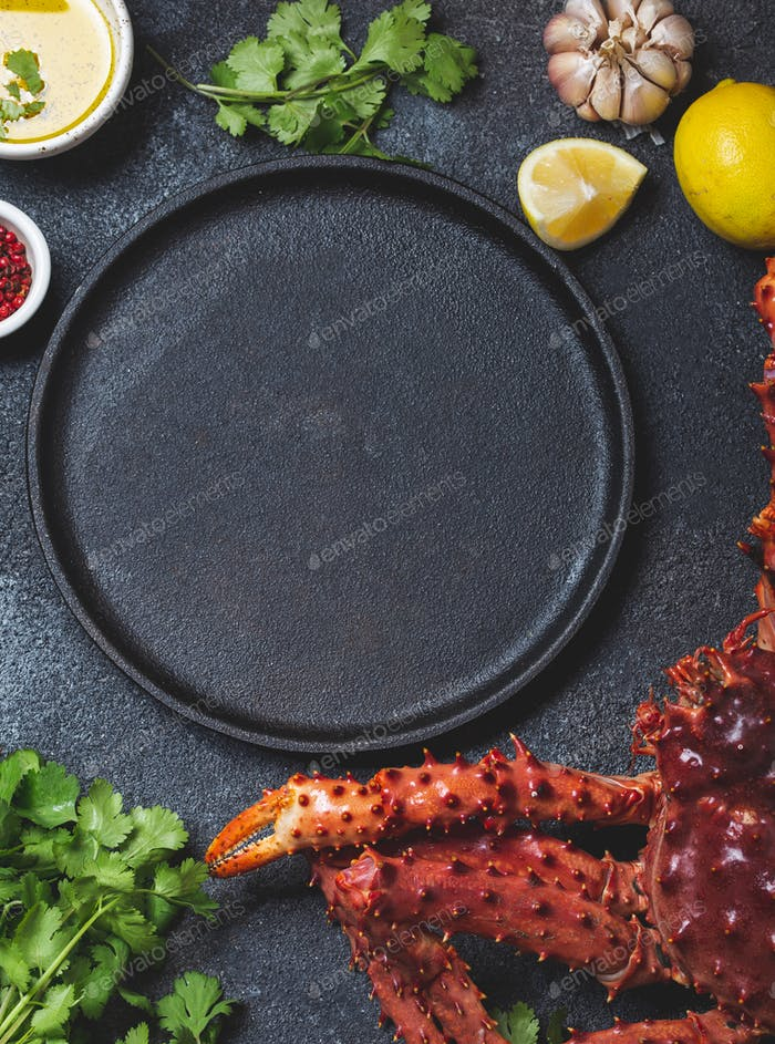 Food background with empty black plate, fresh king crabs, lemons and herbs