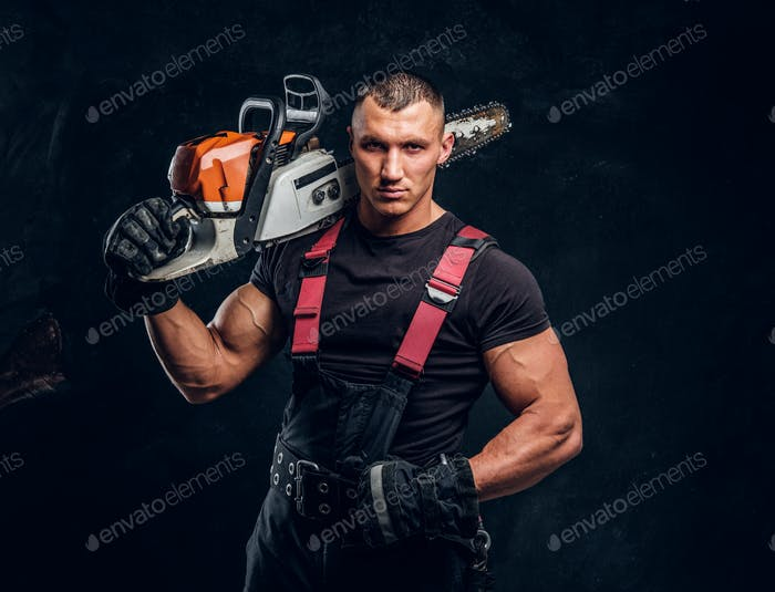 Brutal logger posing with a chainsaw on his shoulder and looking at a camera with a confident look