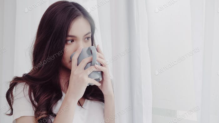 Beautiful teenager female drinking beverage and relax in rainy day.