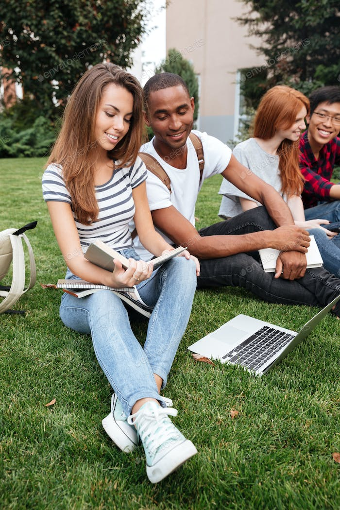 Happy people reading book and using laptop on lawn outdoors