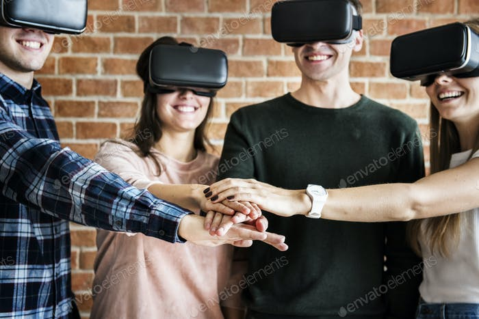 Friends trying on VR headsets and teamwork concept