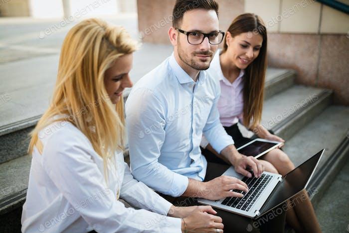 Drei junge lächelnde Kollegen arbeiten zusammen auf Laptop
