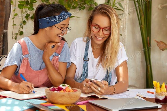 Imagen de estudiantes de raza mixta feliz se comunican durante el proceso de aprendizaje electrónico, escribir información en noteb