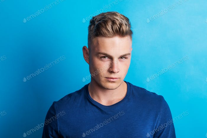 Portrait of a serious thoughtful young man in a studio standing in a studio.