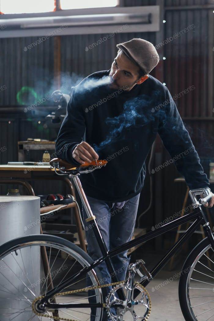 Smoking constructor looking away near bike