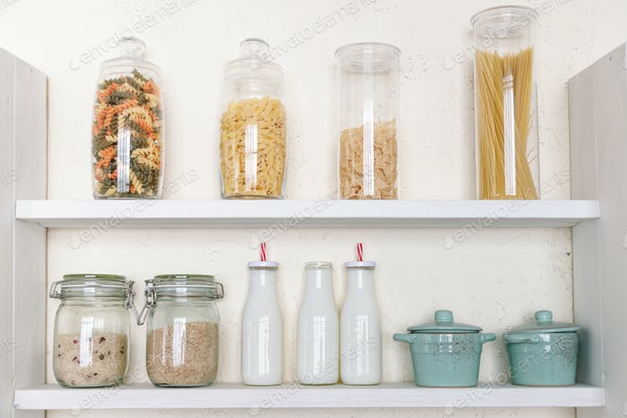 Various uncooked groceries in glass jars on shelf in kitchen