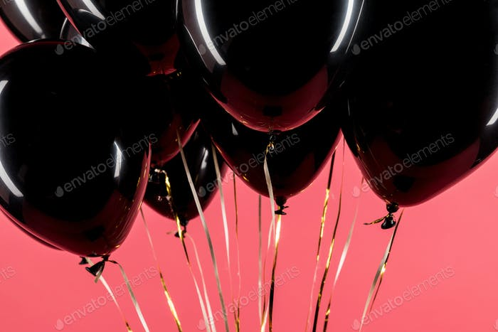 close-up shot of pack of black balloons isolated on red