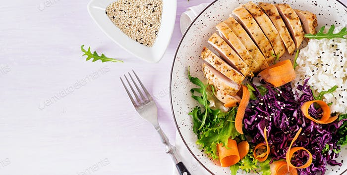Buddha bowl dish with chicken fillet, rice,  red cabbage, carrot, fresh lettuce salad and sesame
