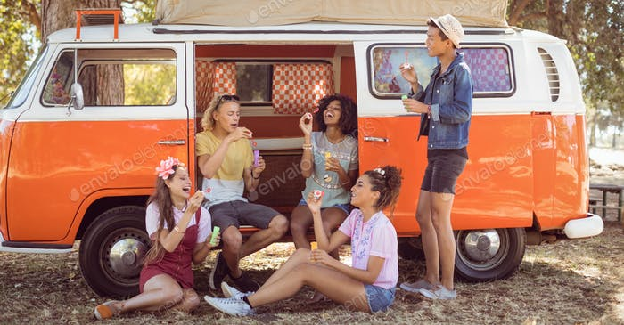 Happy friends enjoying at camper van
