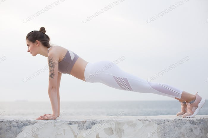 Beautiful girl in sporty top and white leggings practicing yoga