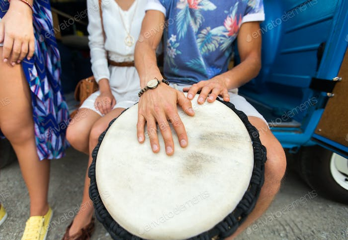 close up of hippie friends playing tom-tom drum