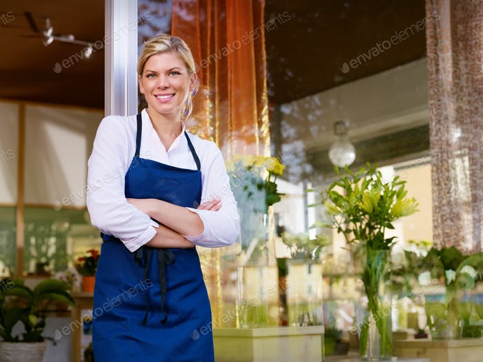Young Pretty Woman Working as Florist in Shop and Smiling