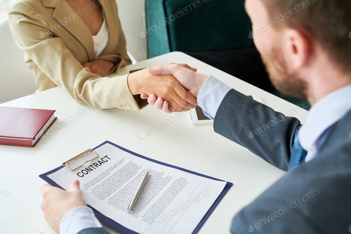 Business People Shaking Hands over Contract