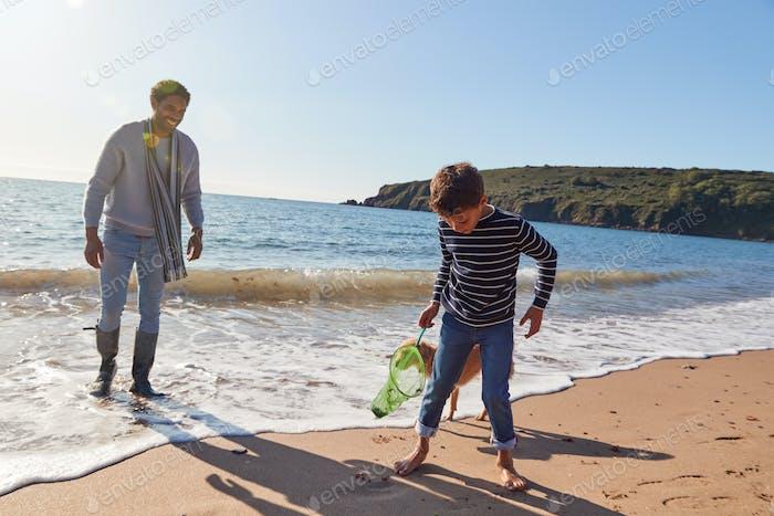 Padre e hijo con perro caminando a lo largo de la playa rompiendo olas en la playa sosteniendo red de pesca