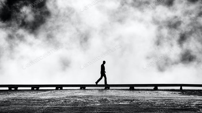 Silhouette of tourist on a footbridge.