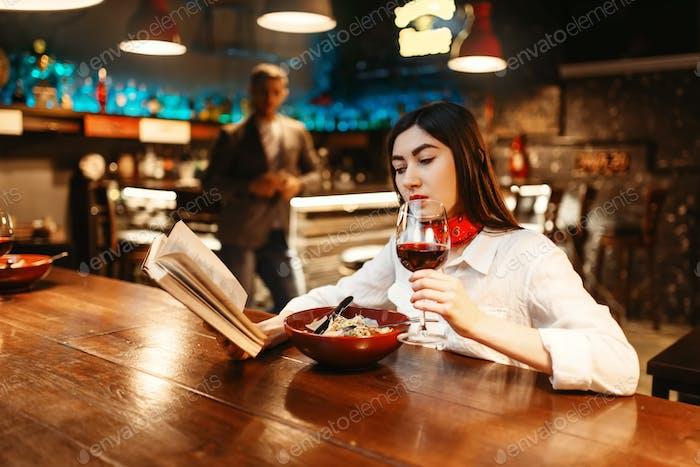 Mujer leyendo un Libro en barra de De madera mostrador