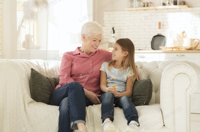 Happy granny with her granddaughter resting together on comfortable sofa indoors