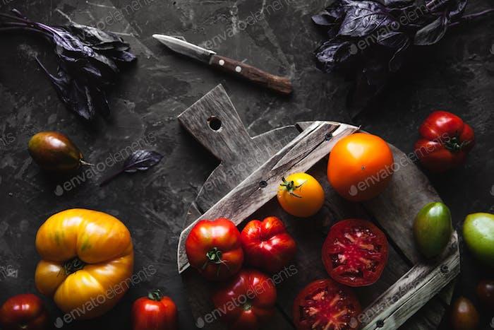 Komposition mit leckeren Tomaten, Holzbrett und Produkten auf grauem Hintergrund