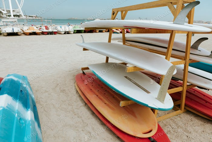 Surfboards stacked on the rack on a beach