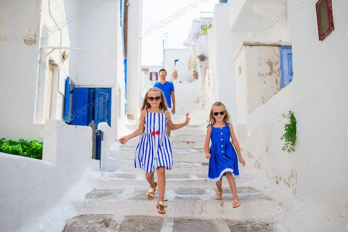 Familienurlaub in Europa. Vater und Kinder auf der Straße des typisch griechischen traditionellen Dorfes auf Mykonos