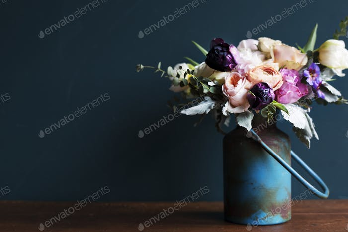 Various fresh flowers arrangement in metalic vase on wooden tabl