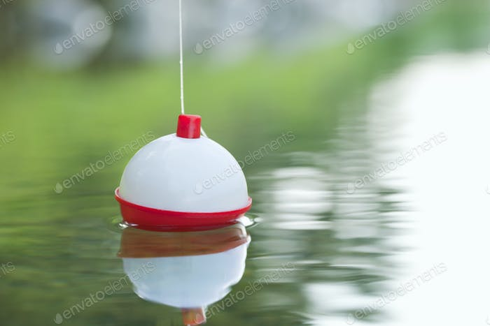 Red and White Bobber Floating in Water