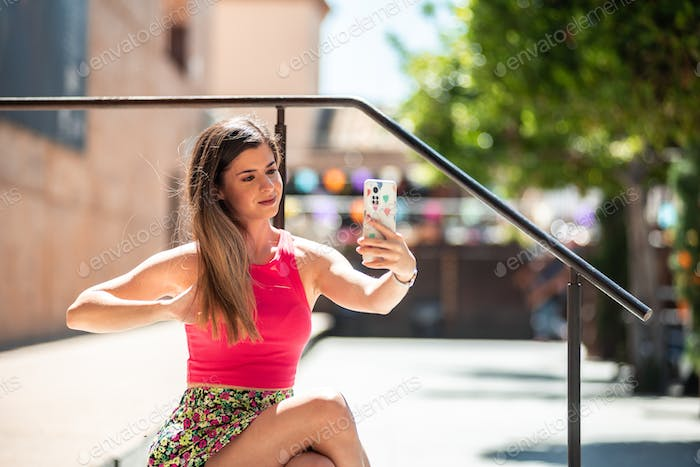 Young blonde girl taking a picture with her mobile phone.