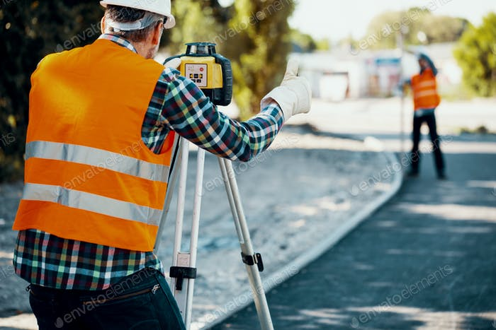 Engineer in reflective vest using equipment during geodetic work
