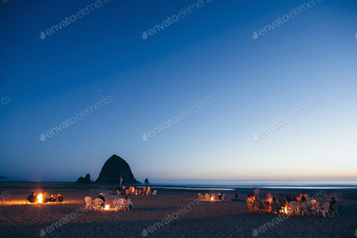 People sitting by campfires on Cannon Beach at dusk. Haystack Rock in the background.