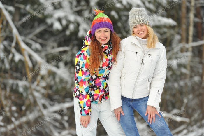 Zwei Mädchen im Winterwald umarmen und lächeln emotional. Glückliche Frauen umarmen und drücken Freude aus